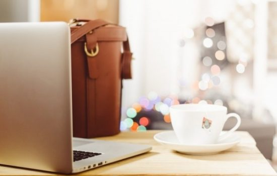 coffee-cup-and-laptop-with-handbag-on-table